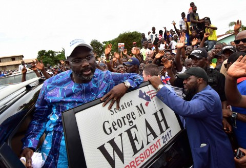 Former international Liberian football star turned politician George Weah, greets supporters during a campaign rally in Monrovia on October 8, 2017, three days ahead of the country's elections.  (Photo:AFP/Issouf Sanogo)