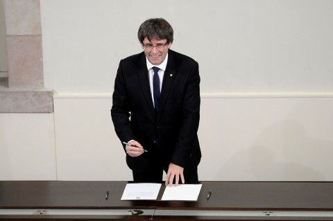Catalan regional government president Carles Puigdemont signs a document about the independence of Catalonia at the Catalan regional parliament in Barcelona on October 10, 2017. (Photo:AFP/Josep Lago)
