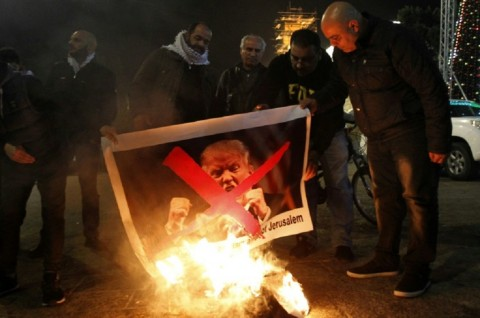 Palestinian protesters burn pictures of US President Donald Trump at Manger Square in the West Bank city of Bethlehem. (Photo: AFP / Musa AL SHAER)
