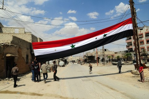 A handout picture released by the official Syrian Arab News Agency (SANA) on April 14, 2018, shows men raising the Syrian flag in a street in the Eastern Ghouta town of Douma after Syrian government forces entered the last rebel bastion. (Photo: AFP/HANDO