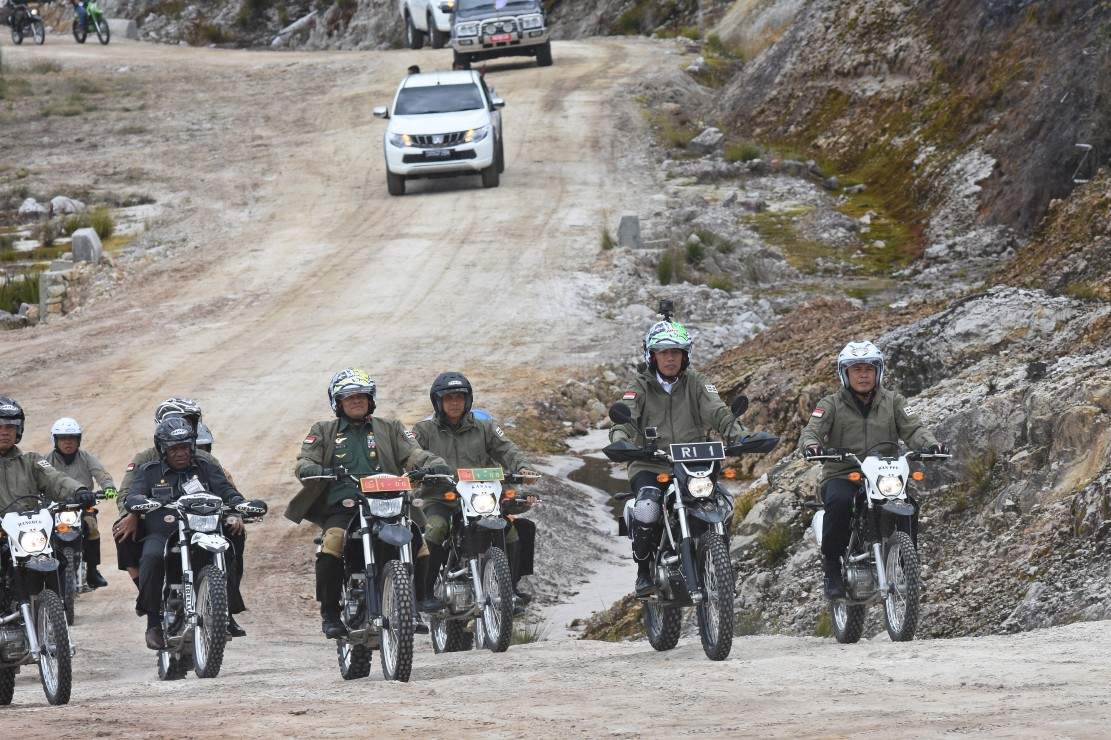 President Joko Widodo, center, rides his own trail bike in a convoy with Indonesian Military Chief Gatot Nurmantyo, left, on a dirt road in the Papua highlands. Image: MetroTVNews